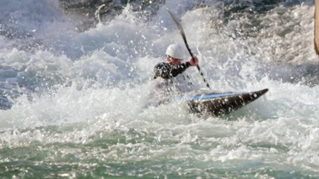 vidéos et rushes de slo mo canoéiste pagayer à travers l'eau vive sur le parcours de slalom - faire du canoë