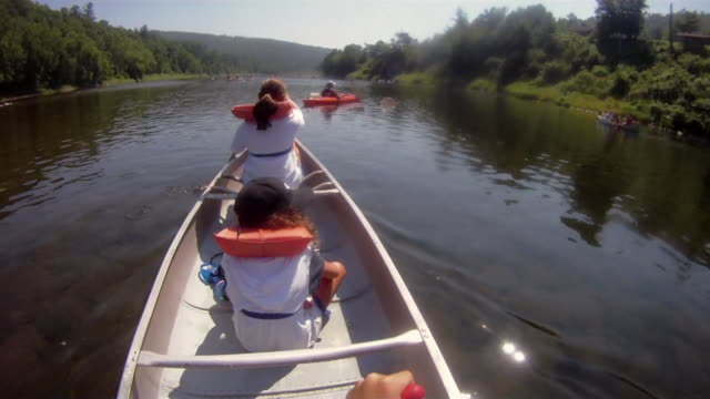 Canoers pass by a kayaker on a lake.