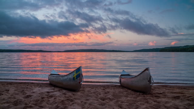 canoes at the beach of a lake at sunset - canoe stock videos & royalty-free footage