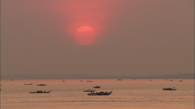 WS Canoes in Mekong River under pink sunrise, Cambodia