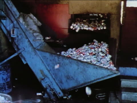 1989 cans being piled into compressor at recycling plant / tilt up stacks of compressed cans / audio - リサイクル工場点の映像素材/bロール