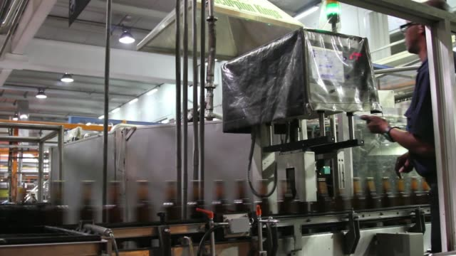 cans of carling black label beer pass along a conveyor belt in the bottling plant at the sabmiller plc brewery in cape town south africa on friday... - beer cap stock videos & royalty-free footage