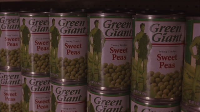 Cans of sweet peas are stacked on shelves at a store.