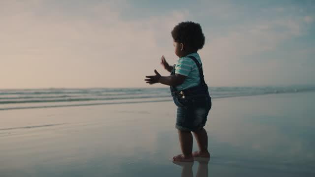 vídeos de stock, filmes e b-roll de não consigo tirar essa areia das minhas mãos. - bebê