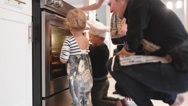 can't wait for cookies to be ready! - children and parents looking inside the electric oven - oven stock videos & royalty-free footage