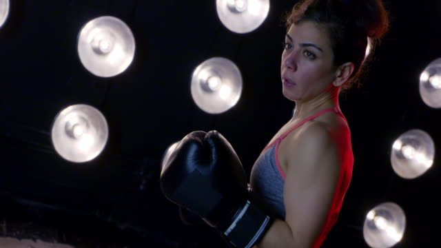 canted angle on young woman in boxing gloves throwing punches 4k - vesper stock stock videos & royalty-free footage