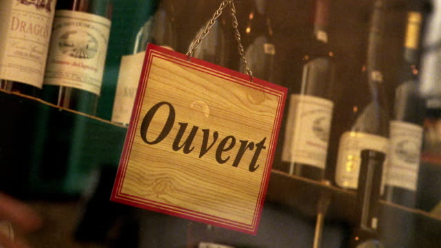 canted close up hand changing sign in window from open to closed in wine store / provence, france - window display stock videos & royalty-free footage