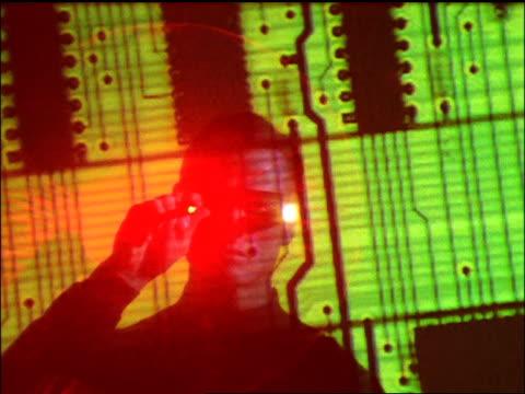 Canted close up man wearing specialized glasses and pointing red laser at circuit board projection