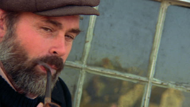 Canted close up portrait middle-aged fisherman smoking pipe next to window / he nods / Nova Scotia