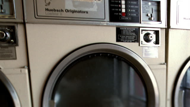 canted close up tilt down clothes dryer in laundromat with clothes spinning / los angeles, california - launderette stock videos and b-roll footage