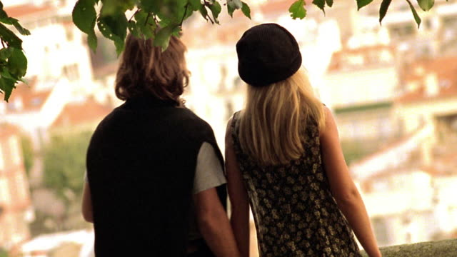 canted medium shot dolly shot rear view couple walking to wall, stopping, and kissing passionately / cannes, france - cannes stock videos & royalty-free footage