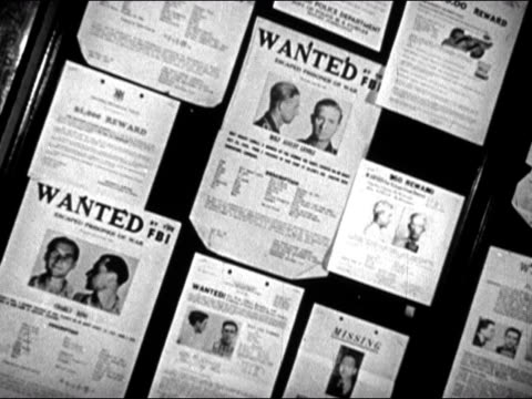 1947 Canted medium shot pan wall of posters showing wanted criminals/ panels turn, revealing more posters/ Dearborn, Michigan