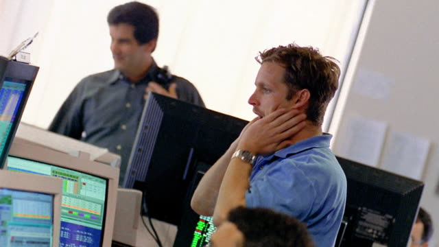 Canted medium shot stressed man standing by computer monitors and talking with other workers