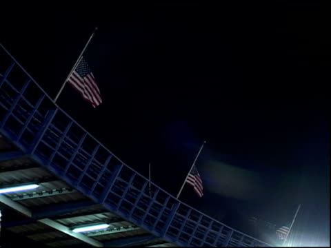 canted view straight view of american flags flying at halfmast against dark sky at shea stadium at first mlb baseball game after september 11... - shea stadium stock videos and b-roll footage