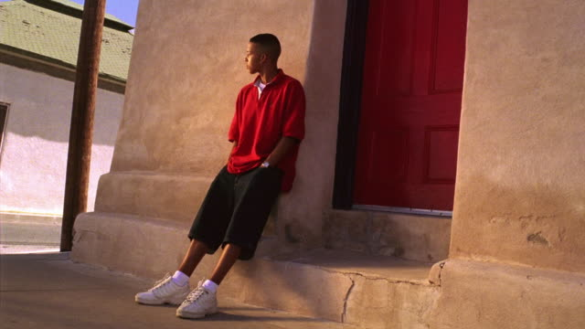 canted wide shot hispanic teenage boy standing to side of doorway looking around / tucson, arizona - one teenage boy only stock videos & royalty-free footage