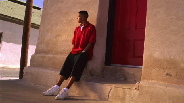 Canted wide shot Hispanic teenage boy standing to side of doorway looking around / Tucson, Arizona