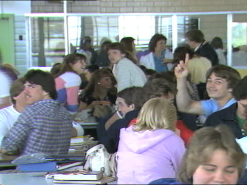 cantonsville senior high school cafeteria packed with teenage caucasian male and female high school students eating, socializing, and waving to the... - female high school student stock videos & royalty-free footage
