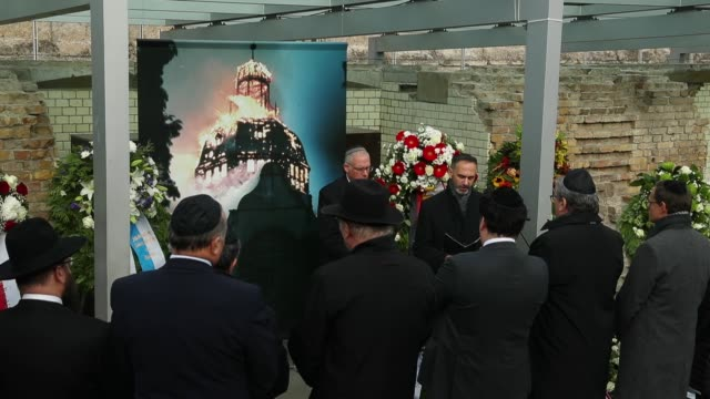 cantor sings while standing next to a photograph of a synagogue burning in 1938 at a ceremony to commemorate the november pogroms, also called... - ゲシュタポ点の映像素材/bロール