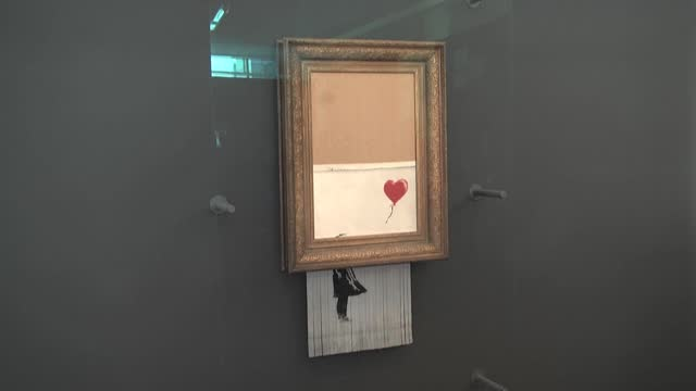 canvas by british artist banksy, which was partially shredded moments after selling at auction in 2018, will go back under the hammer next month,... - report produced segment stock videos & royalty-free footage