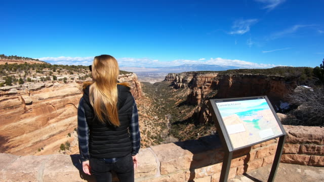 canyon viewpoint, woman with raised hands close to a map - canyon stock-videos und b-roll-filmmaterial