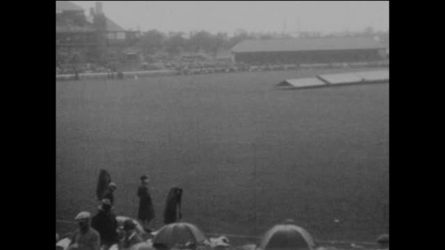 capacity crowd is disappointed, with the umbrellas going up and the covers on the pitch, at old trafford as the first day of the 4th ashes test match... - sport of cricket stock videos & royalty-free footage