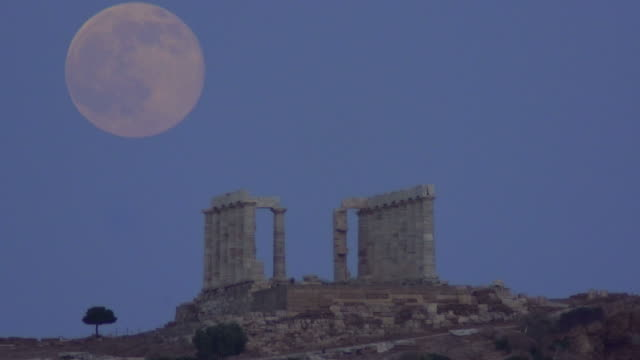 a massive moon rises over the aegean sea and shines down on the ancient temple of poseidon as summer solstice of 2016 coincided with a full moon for... - sounion stock videos and b-roll footage