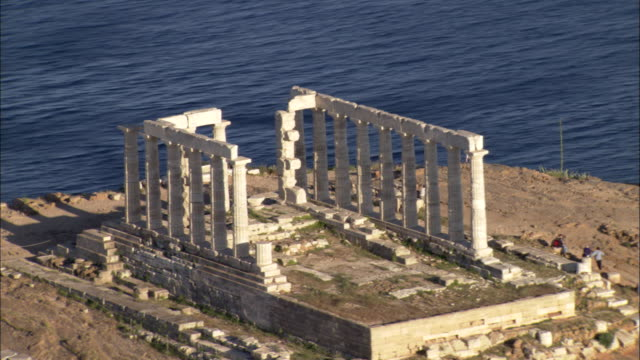 vídeos de stock e filmes b-roll de cape sounion surrounds the ruins of temple of poseidon in greece. - greece