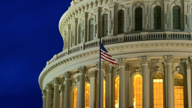 stockvideo's en b-roll-footage met us capital dome at dusk with american flag - senaat verenigde staten