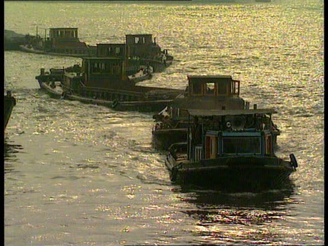 capitalist revival in shanghai; china: shanghai tms barges along river tgv buildings as traffic along wide road gv ditto cms people practising tai... - revival stock videos & royalty-free footage