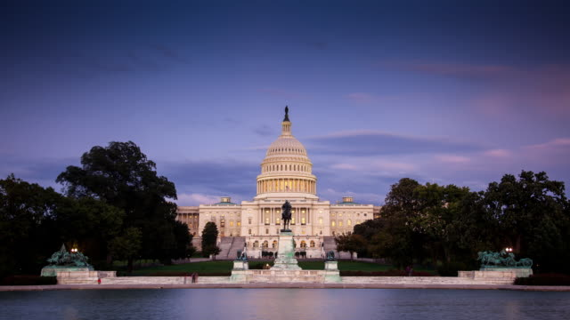 vídeos de stock e filmes b-roll de us capitol building day to night timelapse - washington dc