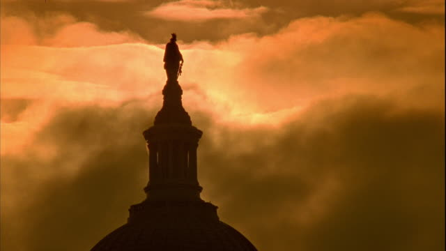 ws capitol building dome top statue of freedom w/ sun behind pillar moving clouds in burnt orange yellow sky - 柱点の映像素材/bロール