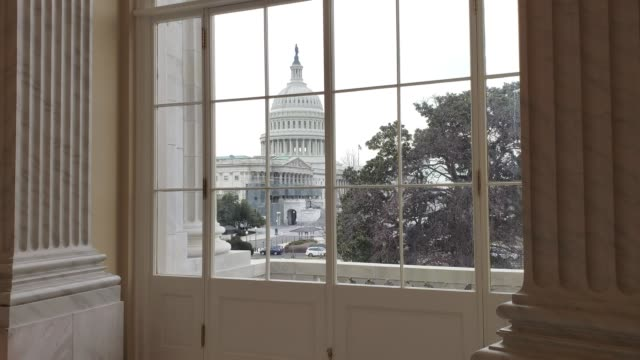 u.s. capitol building east facade from window with american flag in washington, dc - legislator stock videos & royalty-free footage