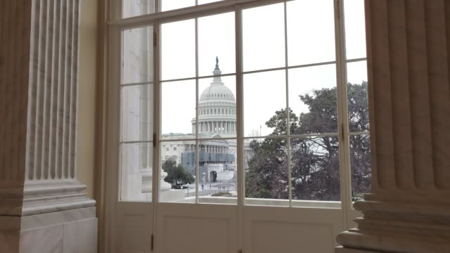 u.s. capitol building east facade from window with american flag in washington, dc - house of representatives stock videos & royalty-free footage