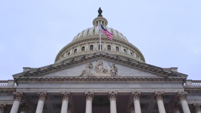 vídeos de stock e filmes b-roll de u.s. capitol building east facade with american flag in washington, dc - senado dos estados unidos