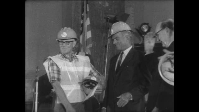 EXT Capitol Building / INT Arkansas farmer hands a hard hat to Senator J William Fulbright and one to Senator John Little McClellan / farmers in hard...