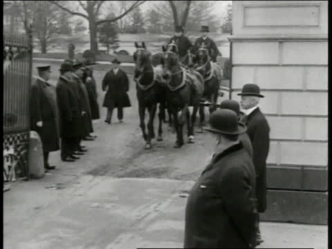 Capitol Building steps crowded w/ people Presidential horse buggy passing MS Men walking along aisle HA WS Woodrow Wilson being sworn in holding then...