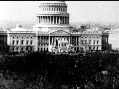 Capitol building w/ crowd below HA MS Convertible w/ outgoing President Woodrow Wilson in back seat sitting next to Presidentelect Warren G Harding...