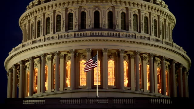 noi capitol dome a notte con bandiera americana-ecu - governo video stock e b–roll