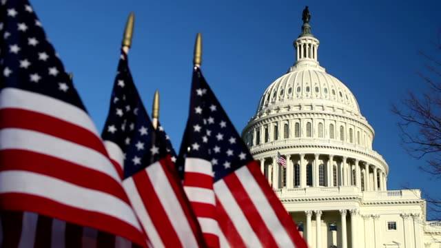 us capitol dome with american flags in foreground - cu - capitol building washington dc stock videos & royalty-free footage