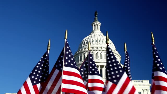 stockvideo's en b-roll-footage met us capitol dome with row of american flags in foreground - republikeinse partij vs