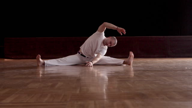 Capoeira athlete warming up and  stretching on parquet floor.