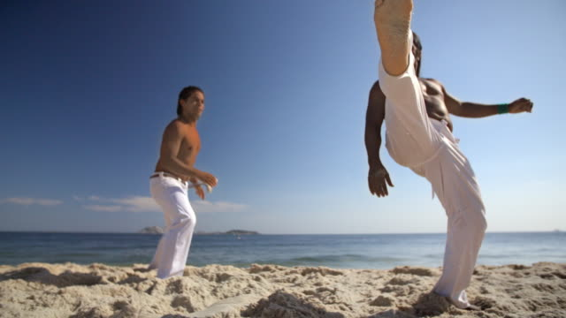 Capoeira fighter on Ipanema Beach kicks sand and claps hands together at camera