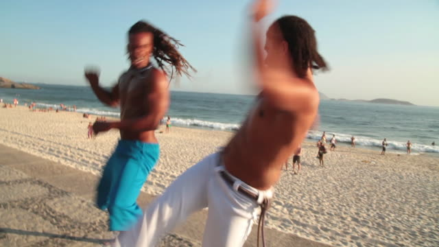 capoeira fighters spar and high-five on ipanema beach boardwalk - martial arts stock videos & royalty-free footage