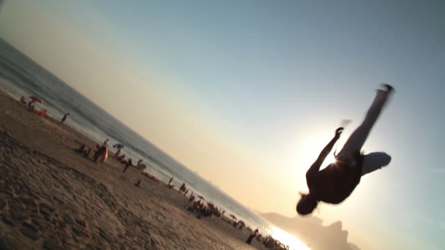capoeira martial artist cartwheels and flips backwards across brazilian beach boardwalk - continuity stock videos & royalty-free footage