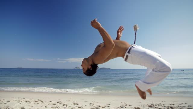 Capoeira martial artist flips backwards in the air on sunny Brazilian beach