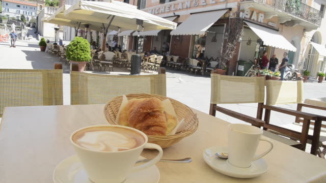 MS Cappuccino coffee and croissant on table at market place / Pietrasanta, Tuscany, Italy