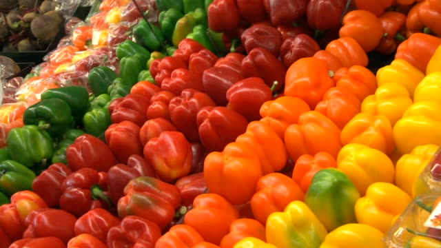 capsicums on display in fresh produce section of supermarket - peperone video stock e b–roll