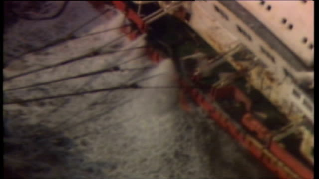 stockvideo's en b-roll-footage met belgium zeebrugge a/s 'herald of free enterprise' upright with cranes over and water pouring out a/s water pouring out of side holes tug against side... - ramp veerboot zeebrugge 1987