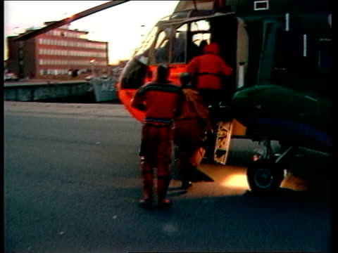 stockvideo's en b-roll-footage met salvage belgium zeebrugge harbour ms divers in wet suits lr on quayside pan lr to bv bv two divers to heli zoom in climb ladder to heli g/a heli in... - zeebrugge