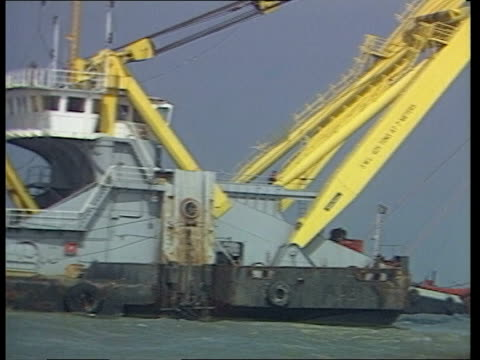 belgium zeebrugge ms tug by side of upturned hull of stricken ferry pan rl steel piles in row in f/g sticking up out of sea ms floating crane pan lr... - zoom out stock videos & royalty-free footage